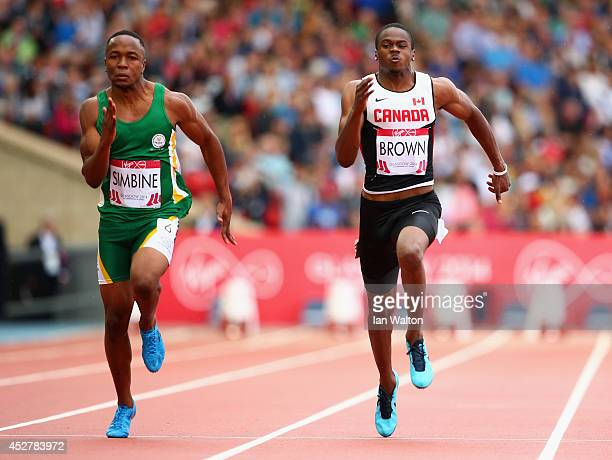 Akani Simbine of South Africa and Aaron Brown of Canada compete in the Men's 100 metres heats at Hampden Park Stadium during day four of the Glasgow...