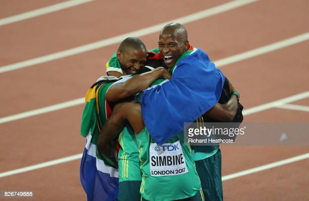 Akani Simbine of South Africa is hugged by long jumpers Luvo Manyonga of South Africa and Ruswahl Samaai of South Africa following the mens 100m...