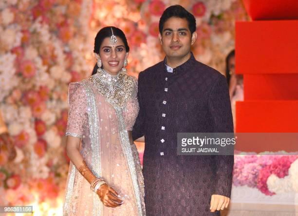 Akash Ambani the eldest son of India's richest man and Reliance Industries Limited Chairman Mukesh Ambani and fiancee Shloka Mehta pose at their...
