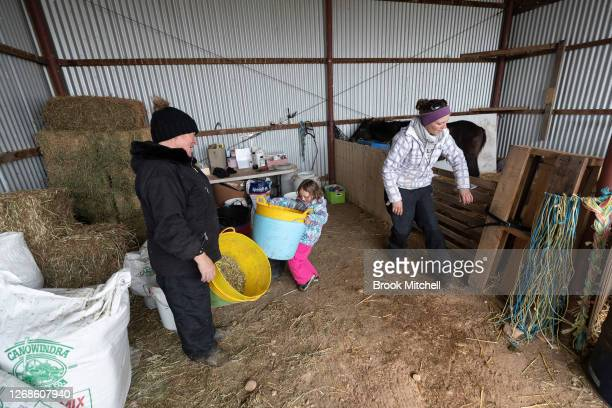 Akayah Walker with mum Mel Yeoman and horse trainer Nikki Alberts work at the White Alpine Equine horse farm in Adaminaby on August 23 2020 in...