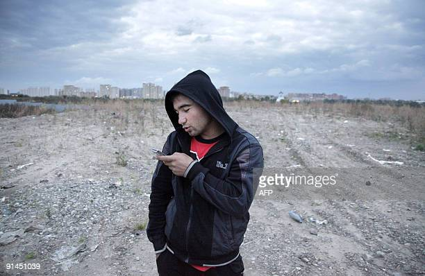 Akbar BORISOV A Tajik migrant worker sends a message on his mobile phone in Moscow on September 23 2009 Stuck working abroad for years at a stretch...