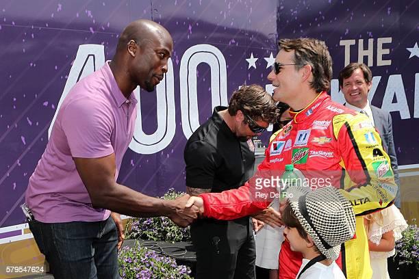 Akbar Gbajabiamila host of American Ninja Warrior talks to Jeff Gordon driver of the Axalta Chevrolet during prerace festivities prior to the NASCAR...