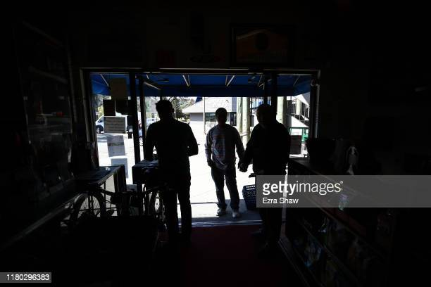 Akber Jiwani the owner of New Bait Shop and David Johnson owner of Davey Jones Market talk to a customer in front of their store darkened by a power...