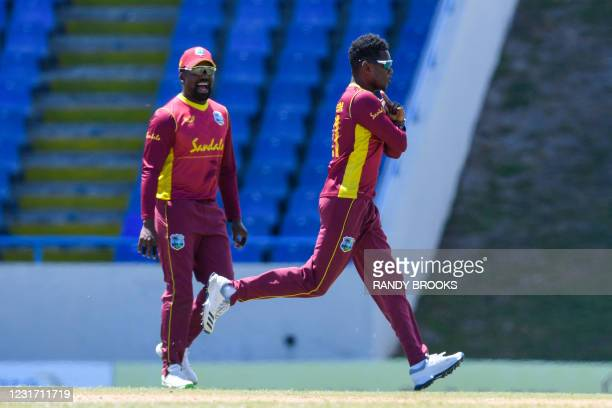 Akeal Hosein and Darren Bravo of West Indies celebrate the dismissal of Dasun Shanaka of Sri Lanka during the 3rd and final ODI match between West...
