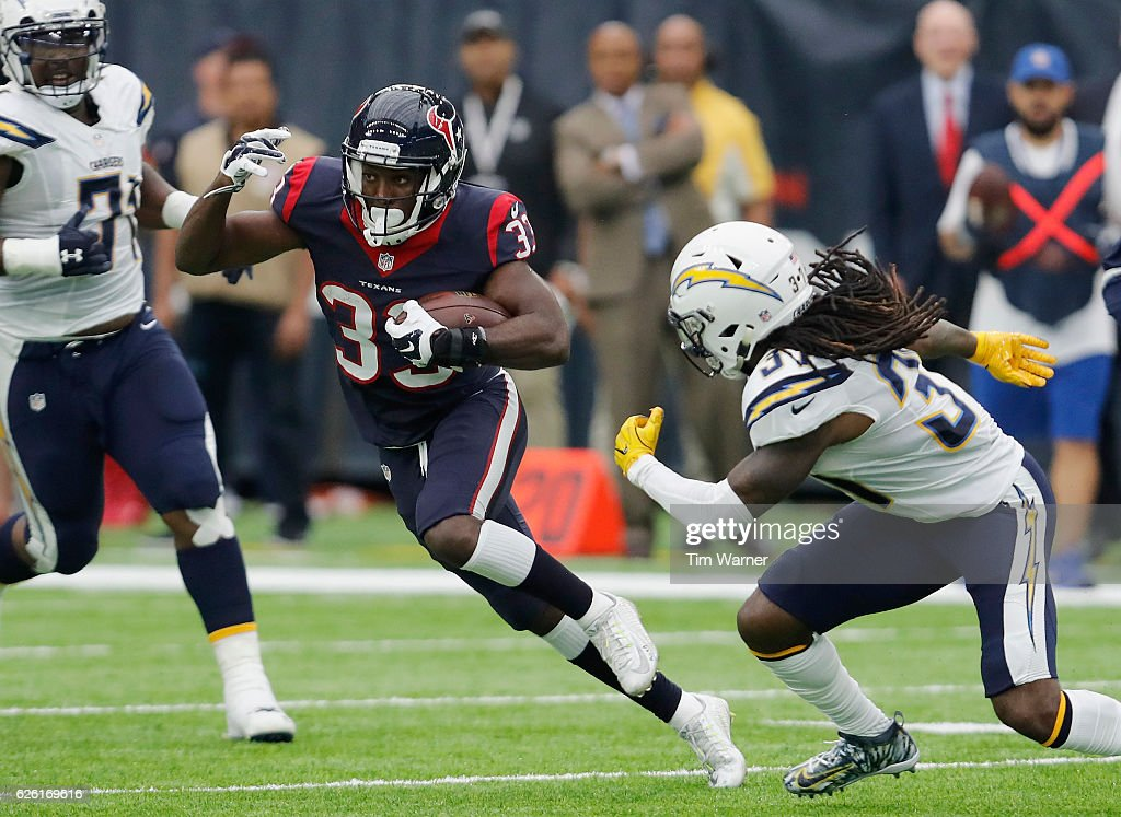 Akeem Hunt #33 of the Houston Texans runs the ball defended by Jahleel Addae #37 of the San Diego Chargers in the first quarter at NRG Stadium on November 27, 2016 in Houston, Texas.