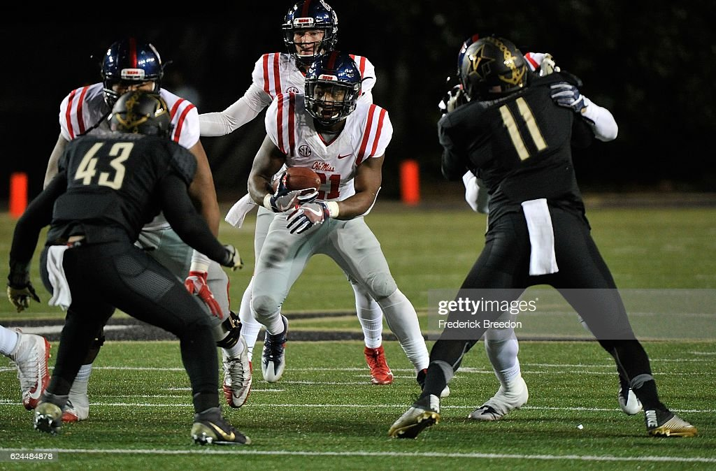 Akeem Judd #21 of the Ole Miss Rebels rushes against Jordan Griffin #43 and Charles Wright #11 of the Vanderbilt Commodores during the first half at Vanderbilt Stadium on November 19, 2016 in Nashville, Tennessee.