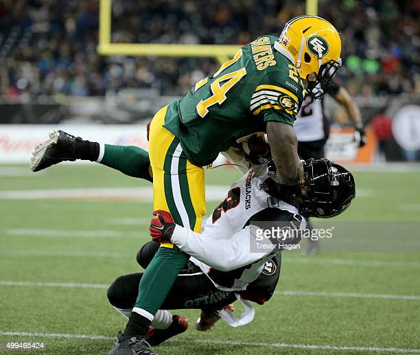 Akeem Shavers of the Edmonton Eskimos' runs over Jovon Johnson of the Ottawa Redblacks during the second half of Grey Cup 103 at Investors Group...