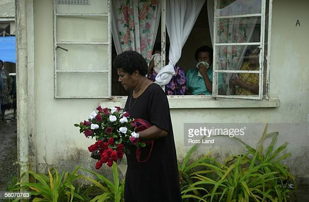 Akeneta Geavula wife of slain policeman Filipo Geavula carries a floral wreath from their home to the police van carrying his coffin on the 5hr drive...
