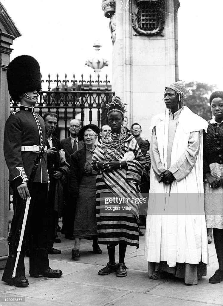 Akenzua II, Oba of Benin, and one of his wives, Queen Oham Akenzua, both dressed in traditional costume, standing beside a Royal Guard at Buckingham Palace, London, 12 August 1950. Queen Oham Akenzua is the youngest of the Benin ruler's eight wives.