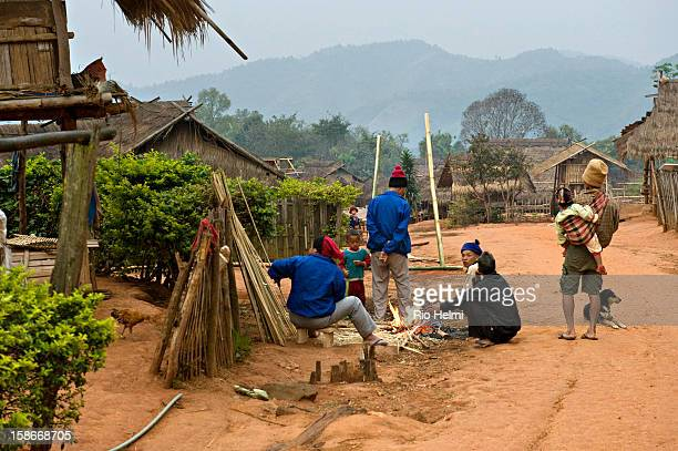 Akha communities are closely knit Early in the morning men chat whilst looking after their children or taking care of chores