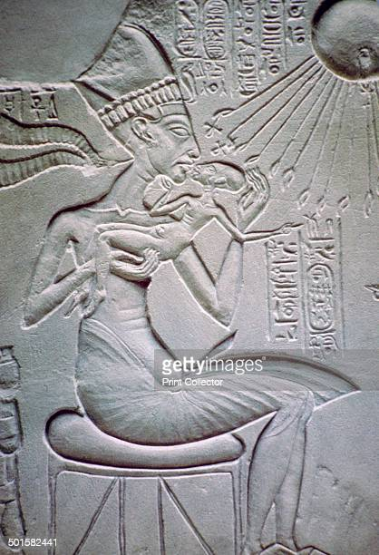 Akhenaten holding one of his daughters beneath the rays of the Sundisk A relief from ElAmarna Egypt Now in the Egyptian Museum Berlin