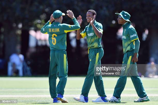 Akhona Mnyaka of South Africa is congratulated by team mates after dismissing Aman Gandhi of Kenya during the ICC U19 Cricket World Cup match between...