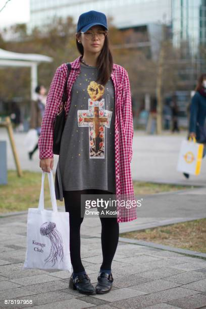 Aki stops for a quick fashion snap wearing a grey Jóueie tshirt featuring a gold cupid on a cross suspended in resin with roses on a starry...