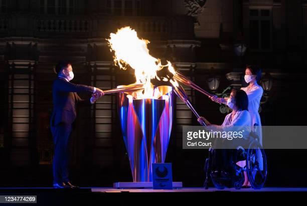 Aki Taguchi , Paralympian and official ambassador of the Tokyo 2020 torch relay, actress Satomi Ishihara and Olympic judoka, Tadahiro Nomura, light...