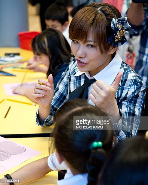 Aki Takajo of Japanese pop group AKB48 interacts with children during a visit to Strong John Thomson Elementary school in Washington on March 26,...
