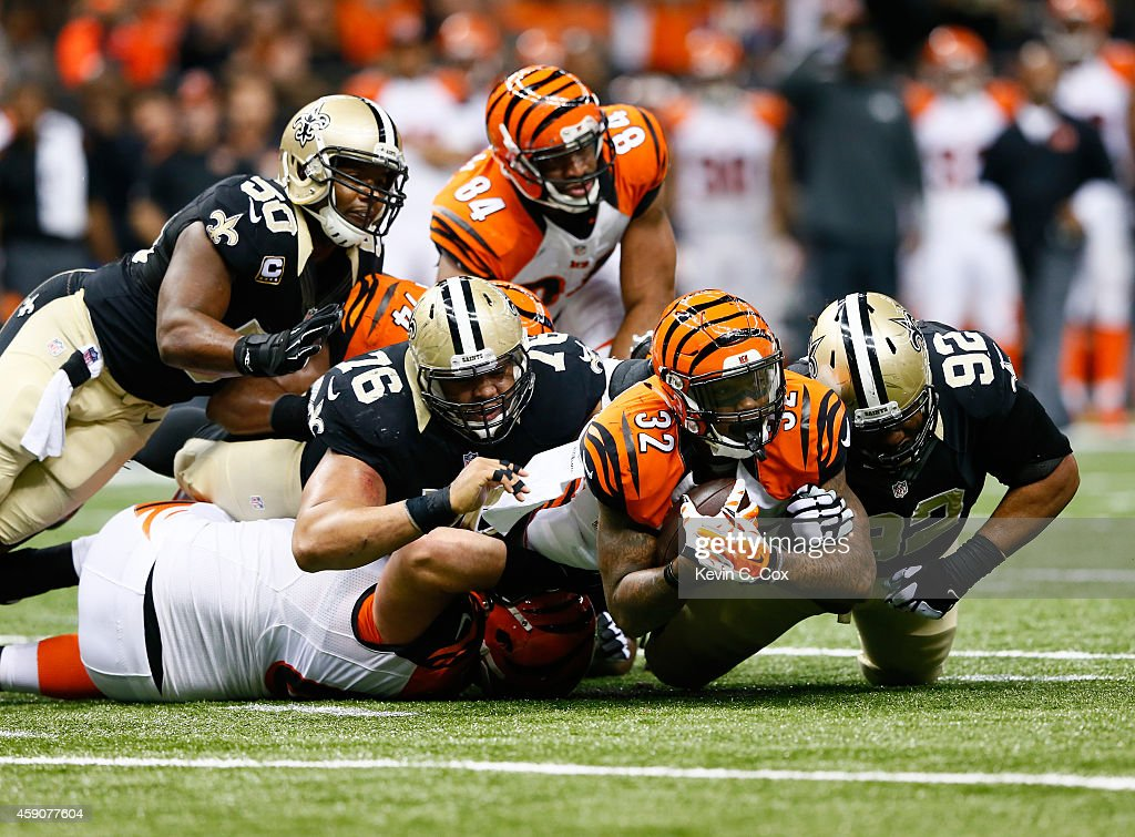 Akiem Hicks #76 of the New Orleans Saints and John Jenkins #92 tackle Jeremy Hill #32 of the Cincinnati Bengals during the first quarter at Mercedes-Benz Superdome on November 16, 2014 in New Orleans, Louisiana.
