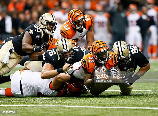 Akiem Hicks of the New Orleans Saints and John Jenkins tackle Jeremy Hill of the Cincinnati Bengals during the first quarter at Mercedes-Benz...