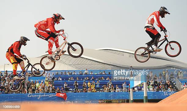 Akifumi Sakamoto of Japan leads Alex Hunter of Hong Kong and Zhao Zhiyang of China in the men's BMX final at the 16th Asian Games in Guangzhou on...