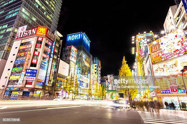 akihabara electric town at night with car light trails at street - anime stock photos and pictures