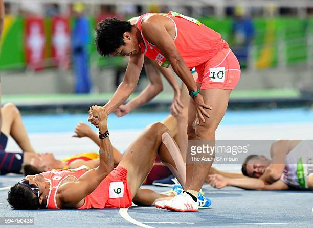 Akihiko Nakamura of Japan shake hands with Keisuke Ushiro after the Men's Decathlon 1500 metres on Day 13 of the Rio 2016 Olympic Games at the...