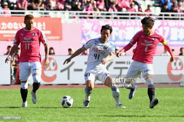 Akihiro Ienaga of Kawasaki Frontale competes for the ball against Souza and Hotaru Yamaguchi of Cerezo Osaka during the JLeague J1 match between...