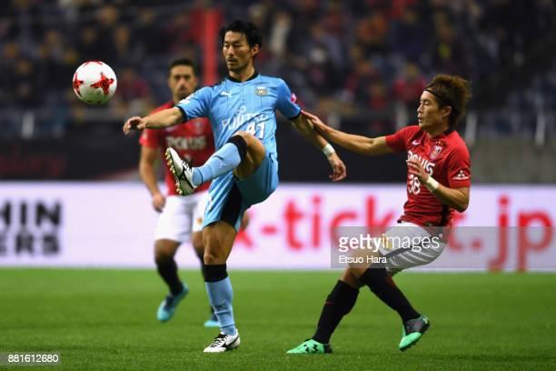 Akihiro Ienaga of Kawasaki Frontale controls the ball under pressure of Daisuke Kikuchi of Urawa Red Diamonds during the J.League J1 match between...