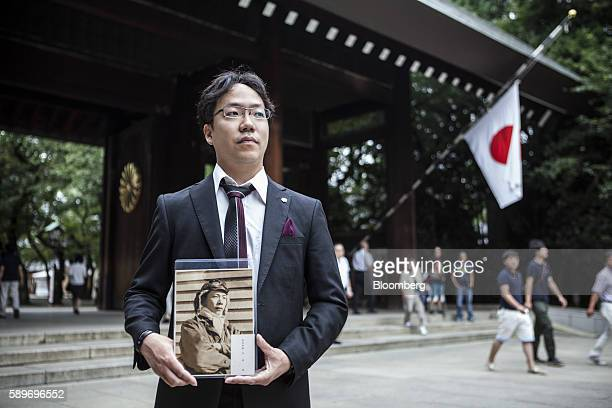 Akihiro Kato holds a portrait of his grandfather who served in World War II during a visit to the Yasukuni Shrine on the anniversary of Japan's World...