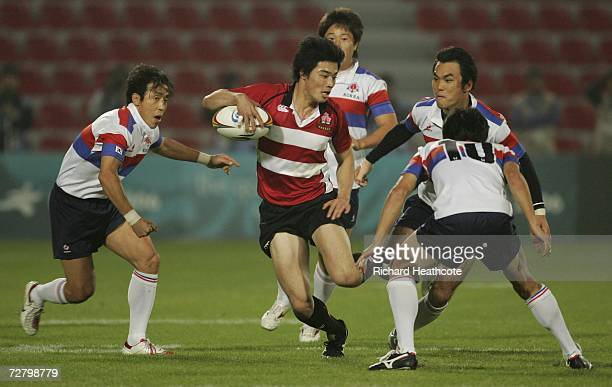 Akihito Yamada of Japan breaks through the Korean defence to score a try during the Rugby 7's Final during the 15th Asian Games Doha 2006 at the...