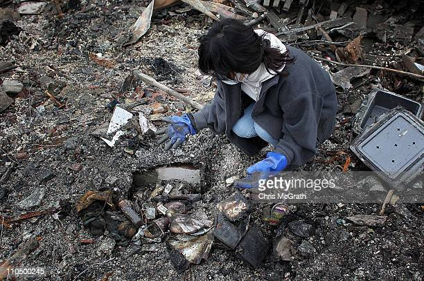 Akiko Hatareyama digs for any salvagable items from her burnt out home on March 21 2011 in Kesennuma Japan The 90 magnitude strong earthquake struck...