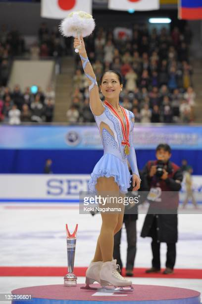 Akiko Suzuki of Japan waves for fans on the podium at the medal ceremony during day two of the ISU Grand Prix of Figure Skating NHK Trophy at...