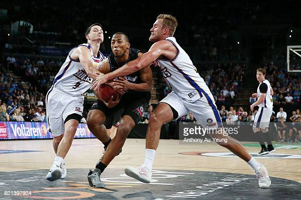 Akil Mitchell of New Zealand is fouled by Shaun Bruce and Mitchell Young of Brisbane during the round five NBL match between the New Zealand Breakers...