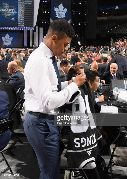 Akil Thomas puts on his jersey after being selected 51st overall by the Los Angeles Kings during the 2018 NHL Draft at American Airlines Center on...