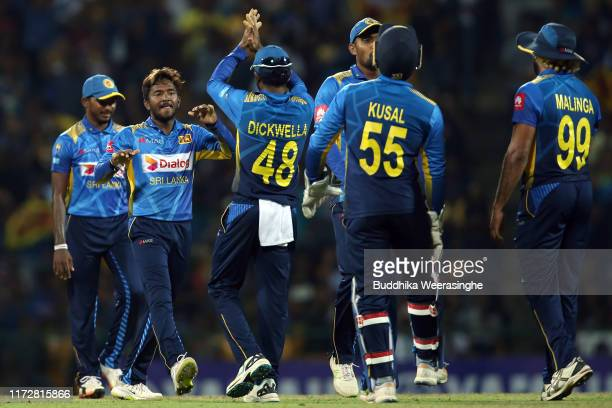 Akila Dananjaya of Sri Lanka celebrates with team mates after taking a wicket of Mitchell Santner of New Zealand during the Twenty20 International...