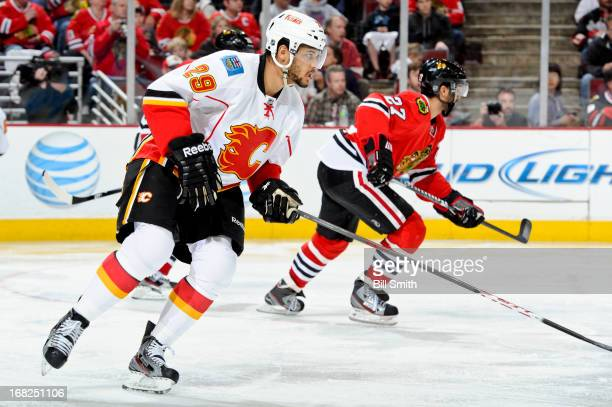 Akim Aliu of the Calgary Flames and Johnny Oduya of the Chicago Blackhawks skate up the ice during the NHL game on April 26 2013 at the United Center...