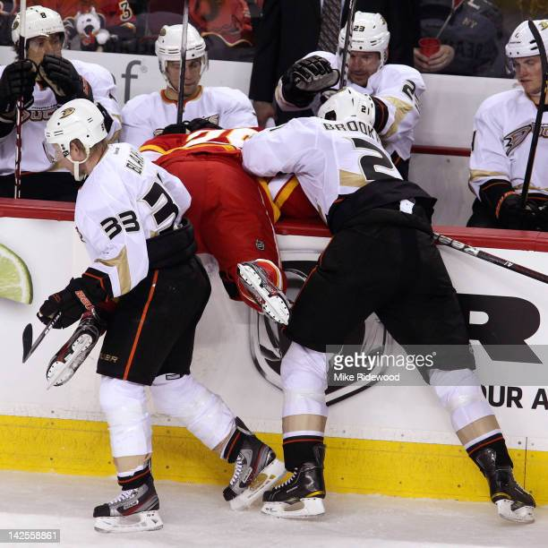 Akim Aliu of the Calgary Flames is dumped into the bench by Sheldon Brookbank and Jason Blake of the Anaheim Ducks during second period NHL action on...