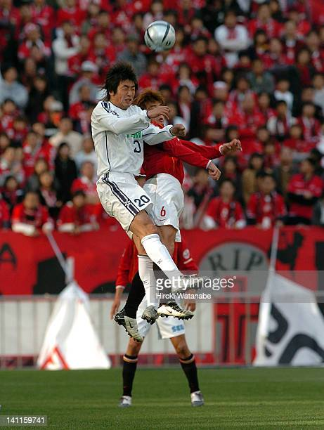 Akinori Nishizawa of Cerezo Osaka and Nobuhisa Yamada of Urawa Red Diamonds compete for the ball during the JLeague match between Urawa Red Diamonds...