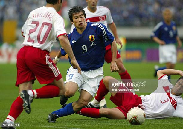 Akinori Nishizawa of Japan is tackled by Bulent Korkmaz of Turkey during the FIFA World Cup Korea/Japan round of 16 match between Japan and Turkey at...