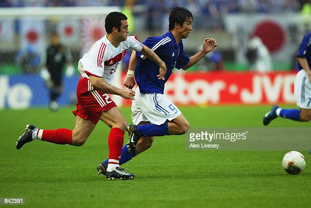Akinori Nishizawa of Japan takes the ball past Hakan Unsal of Turkey during the FIFA World Cup Finals 2002 Second Round match played at the Miyagi...