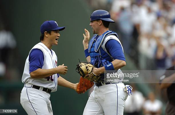Akinori Otsuka and Chris Stewart of the Texas Rangers celebrate following the game against the Toronto Blue Jays at Rangers Ballpark in Arlington in...