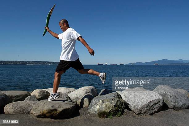 Akio Tayler of the Canadian National Rugby Team carries the Melbourne 2006 Queen's Baton as he leaps over rocks at English Bay September 11 2005 in...