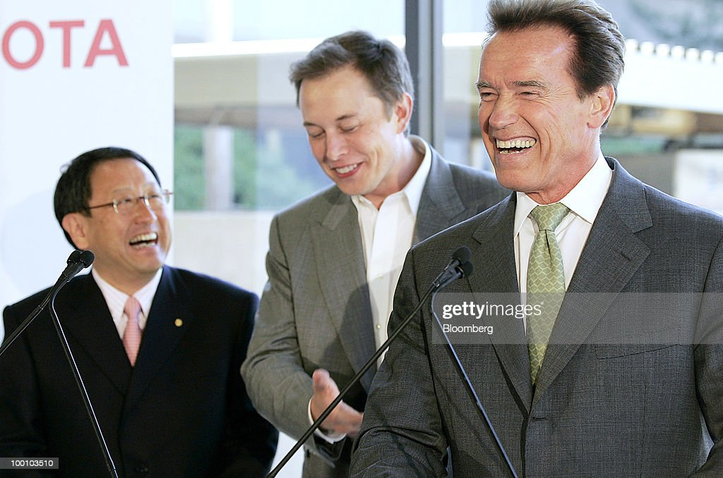 Akio Toyoda, president of Toyota Motor Corp., left, Elon Musk, chairman and chief executive officer of Tesla Motors Inc., center, and Arnold Schwarzenegger, governor of California, laugh during a news conference at Tesla Motors Inc.'s headquarters in Palo Alto, California, U.S., on Thursday, May 20, 2010. Toyota Motor Corp. will acquire a $50 million stake in California electric-car maker Tesla Motors Inc. as automakers compete to introduce less-polluting vehicles in the U.S. Photographer: Tony Avelar/Bloomberg via Getty Images