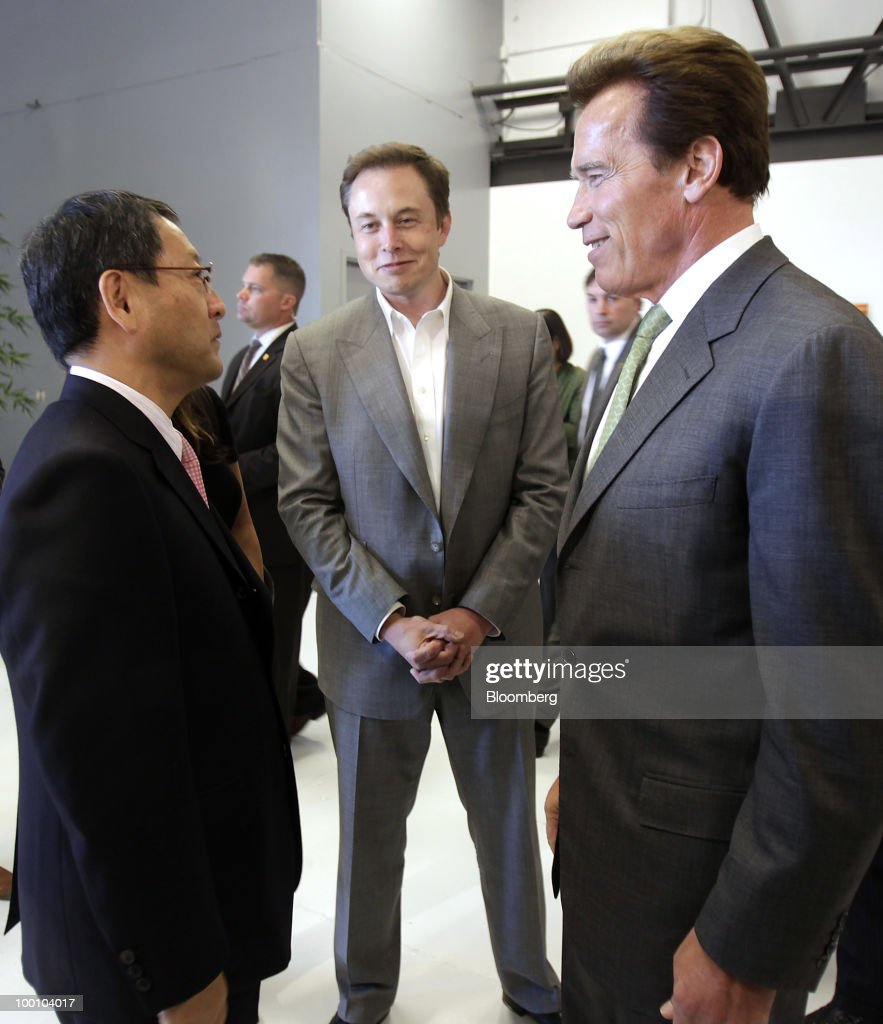 Akio Toyoda, president of Toyota Motor Corp., left, Elon Musk, chairman and chief executive officer of Tesla Motors Inc., center, and Arnold Schwarzenegger, governor of California, chat at Tesla Motors Inc.'s headquarters in Palo Alto, California, U.S., on Thursday, May 20, 2010. Toyota Motor Corp. will acquire a $50 million stake in California electric-car maker Tesla Motors Inc. as automakers compete to introduce less-polluting vehicles in the U.S. Photographer: Tony Avelar/Bloomberg via Getty Images