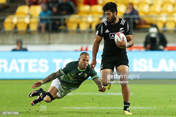 Akira Ioane of New Zealand beats the tackle of Francois Hougaard of South Africa on his way to scoring a try during the 2016 Wellington Sevens pool...