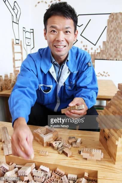 Akira Kuwabara president of New Tech Shinsei Inc shows how to play 'Mokulock' wooden building blocks for children in Yonezawa Yamagata Prefecture on...