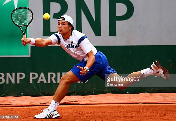 Akira Santillan of Japan returns a shot during his boys' singles match against Alex Molcan of Slovakia on day eight of the 2015 French Open at Roland...