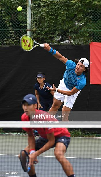 Akira Santillan of Japan serves during the men's doubles first round match against Tomas Berdych and Radek Stepanek of the Czech Republic on day two...