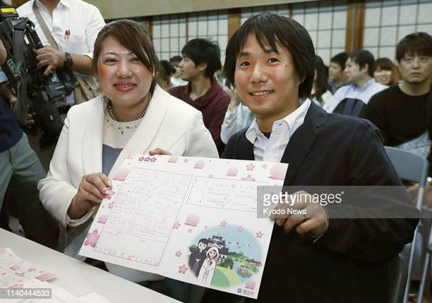 Akira Tomimatsu and his wife Yoko show a copy of their marriage certificate at Okayama Castle on May 1 the first day of Japan's new imperial era...