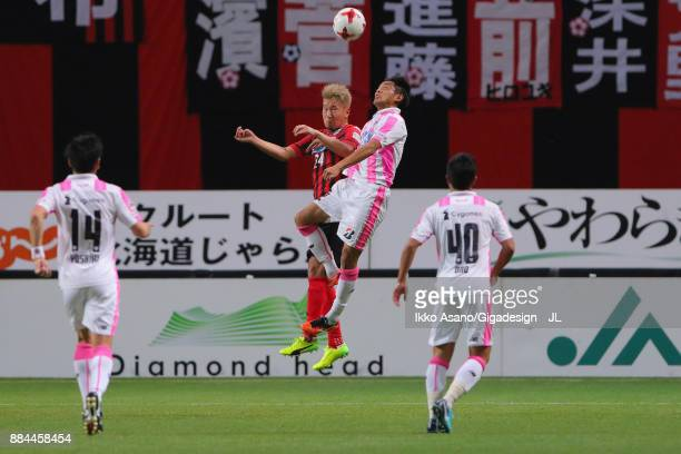 Akito Fukumori of Consadole Sapporo and Kei Ikeda of Sagan Tosu compete for the ball during the JLeague J1 match between Consadole Sapporo and Sagan...