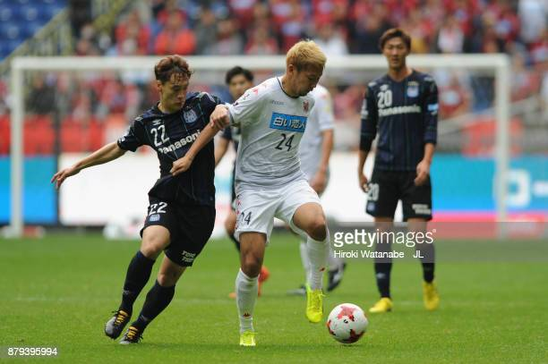 Akito Fukumori of Consadole Sapporo and Oh Jae Suk of Gamba Osaka compete for the ball during the JLeague J1 match between Gamba Osaka and Consadole...