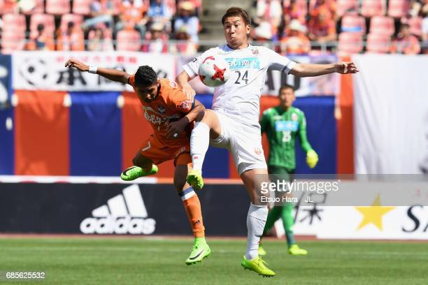 Akito Fukumori of Consadole Sapporo and Rony of Albirex Niigata compete for the ball during the JLeague J1 match between Albirex Niigata and...
